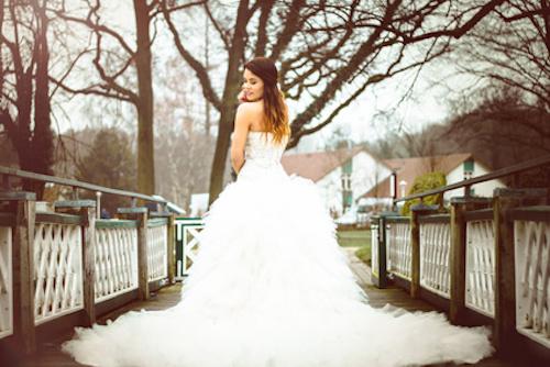 Frau im Brautkleid auf einer Brücke